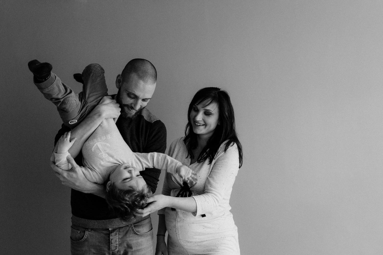 photographe de famille, papa, maman et bébé jouent